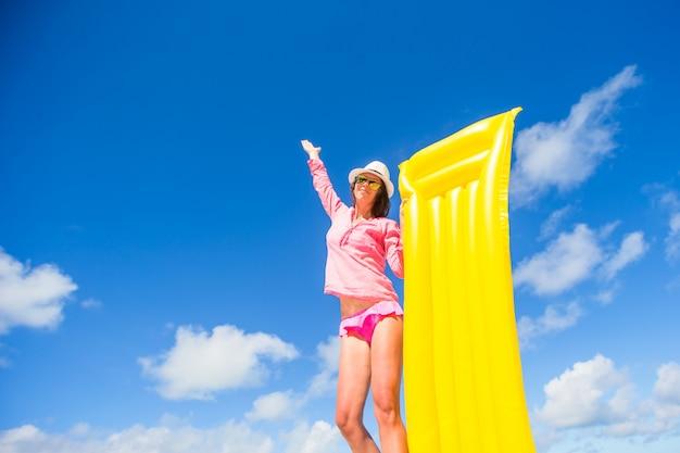 Jeune femme heureuse se détendre avec un matelas pneumatique sur la plage Photo Premium