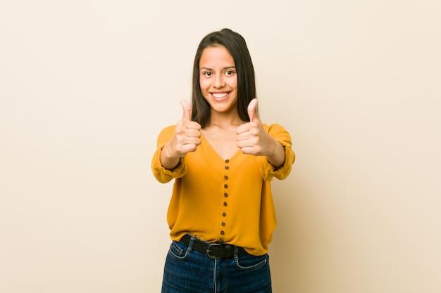 Jeune Femme Hispanique Contre Un Mur Beige Avec Le Pouce Levé, Applaudit à Quelque Chose, Soutient Et Respecte Le Concept. Photo Premium