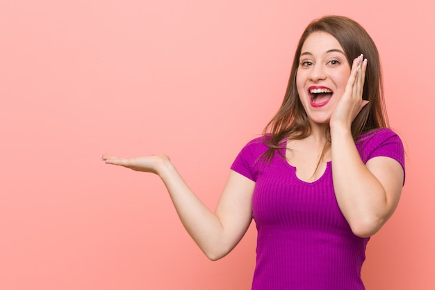 Jeune femme hispanique contre un mur rose, espace de copie sur une paume, garde la main sur la joue. étonné et ravi. Photo Premium