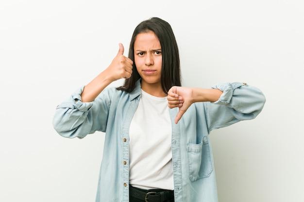 Jeune femme hispanique montrant les pouces vers le haut et vers le bas, difficile de choisir Photo Premium