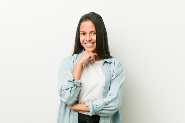 Jeune femme hispanique souriante heureuse et confiante, toucher le menton avec la main. Photo Premium