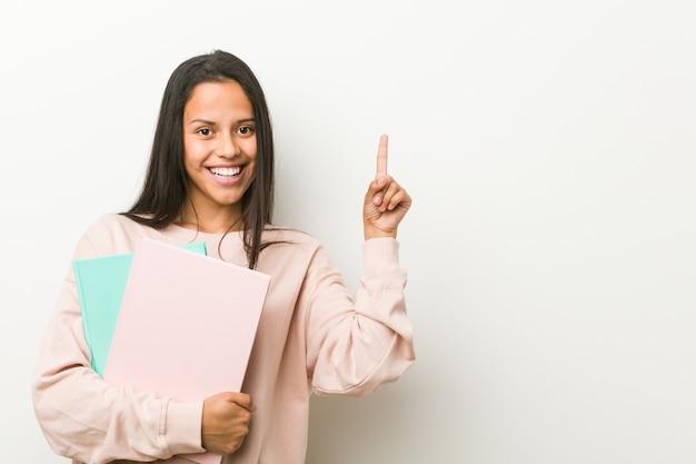 Jeune femme hispanique tenant des cahiers souriant, pointant gaiement avec l'index. Photo Premium