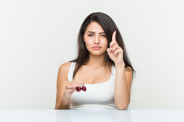 Jeune femme hispanique tenant des cerises montrant le numéro un avec le doigt. Photo Premium