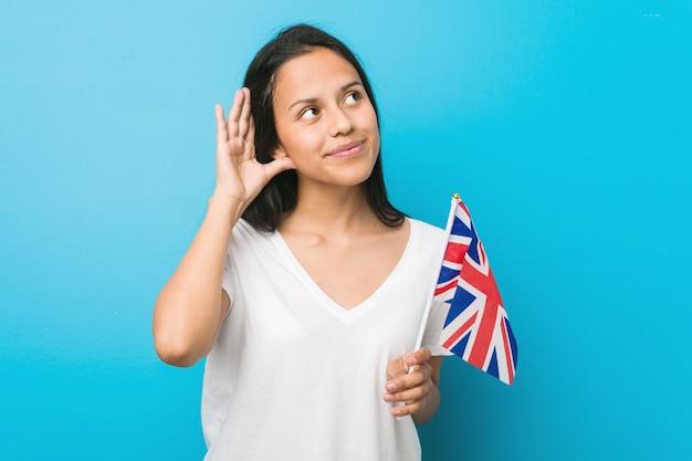 Jeune femme hispanique tenant un drapeau du royaume-uni essayant d'écouter un commérage. Photo Premium