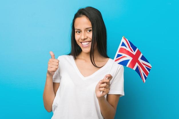 Jeune femme hispanique tenant un drapeau du royaume-uni souriant et levant le pouce vers le haut Photo Premium