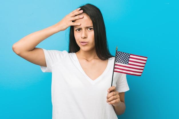 Jeune femme hispanique tenant un drapeau des états-unis sous le choc, elle s'est souvenue d'une réunion importante. Photo Premium