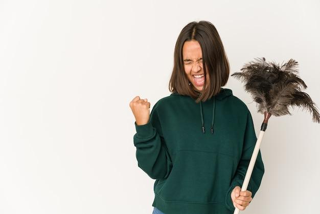 Jeune Femme Hispanique Tenant Un Plumeau En Levant Le Poing Après Une Victoire, Concept Gagnant. Photo Premium