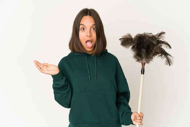 Jeune Femme Hispanique Tenant Un Plumeau Surpris Et Choqué. Photo Premium