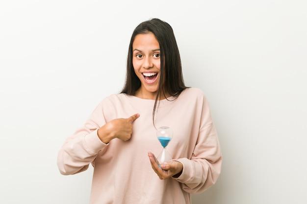 Jeune femme hispanique tenant un sablier surpris, se montrant du doigt, souriant largement. Photo Premium