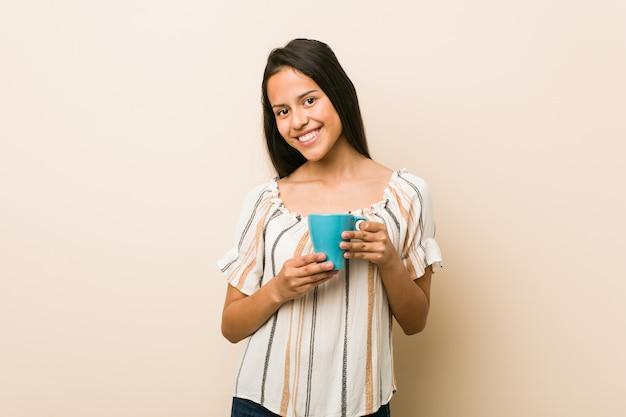 Jeune femme hispanique tenant une tasse heureuse, souriante et gaie. Photo Premium