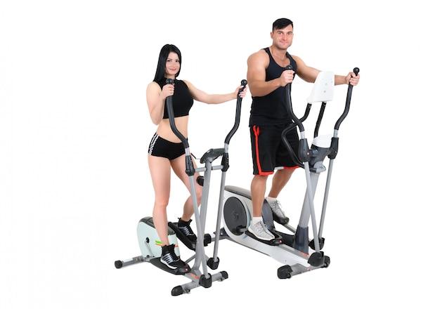 Jeune femme et homme faisant des exercices sur vélo elliptique Photo Premium