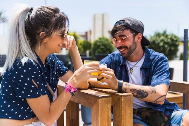 Jeune femme et homme parlant et buvant des boissons Photo gratuit