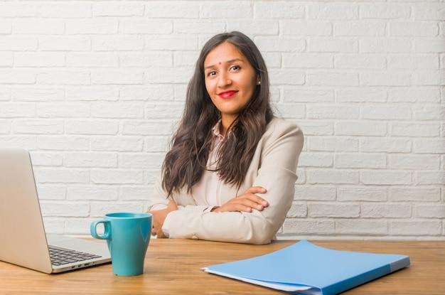 Jeune femme indienne au bureau croisant les bras, souriante et heureuse, confiante et amicale Photo Premium