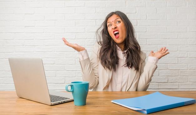 Jeune femme indienne au bureau folle et désespérée, criant hors de contrôle, drôle lunatique exprimant la liberté et sauvage Photo Premium