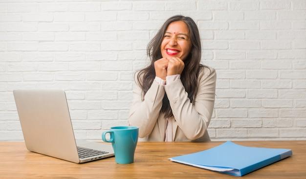 Jeune femme indienne au bureau très heureuse et excitée, levant les bras, célébrant une victoire ou un succès, remportant le tirage au sort Photo Premium