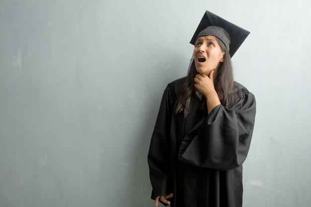 Jeune femme indienne diplômée contre un mur inquiet et accablé, pression de sentiment anxieux, concept d'angoisse Photo Premium