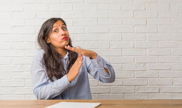 Jeune femme indienne fatiguée et ennuyée, faisant un geste de temporisation, doit arrêter en raison du stress au travail Photo Premium