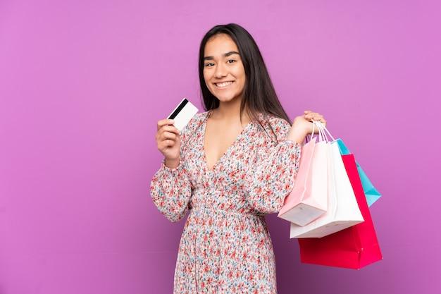 Jeune Femme Indienne Isolée Sur Un Mur Violet Tenant Des Sacs à Provisions Et Une Carte De Crédit Photo Premium