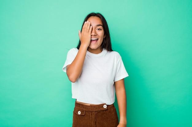 Jeune Femme Indienne Métisse Isolée S'amusant à Cône La Moitié Du Visage Avec La Paume. Photo Premium
