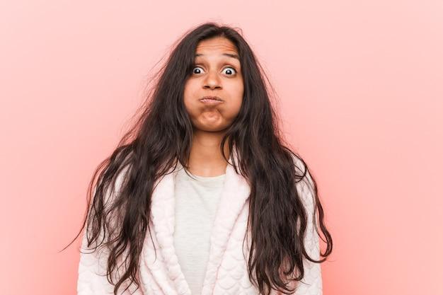 Jeune Femme Indienne Portant Un Pyjama Souffle Sur Les Joues, A Une Expression Fatiguée. Photo Premium