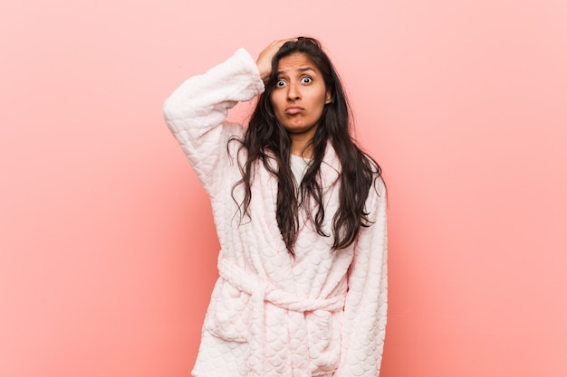 Jeune femme indienne en pyjama étant sous le choc, il s'est souvenu d'une réunion importante. Photo Premium