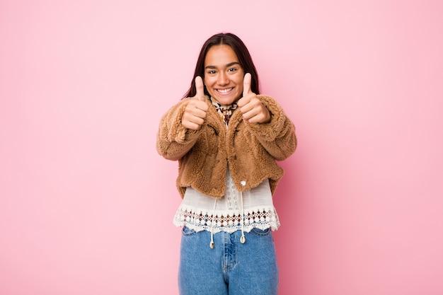 Jeune Femme Indienne De Race Mixte Portant Un Manteau Court En Peau De Mouton Avec Les Pouces Vers Le Haut, Applaudit à Quelque Chose, Soutient Et Respecte Le Concept. Photo Premium