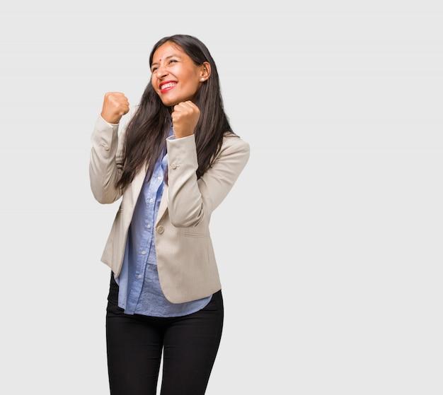 Jeune femme indienne très heureuse et excitée, levant les bras, célébrant une victoire ou un succès, remportant le tirage au sort Photo Premium