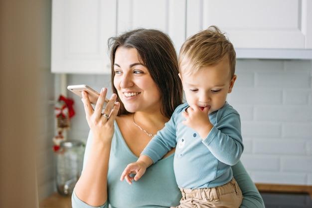 La jeune femme insouciante maman avec bébé garçon dans les mains dicte un message vocal sur téléphone mobile dans une cuisine lumineuse Photo Premium