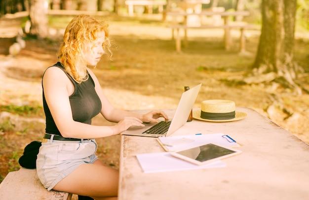 Jeune femme sur internet dans un parc Photo gratuit