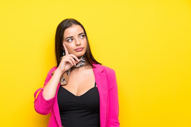Jeune femme sur jaune isolé, pensant une idée Photo Premium