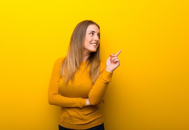 Jeune femme jaune pointant une bonne idée et levant les yeux Photo Premium