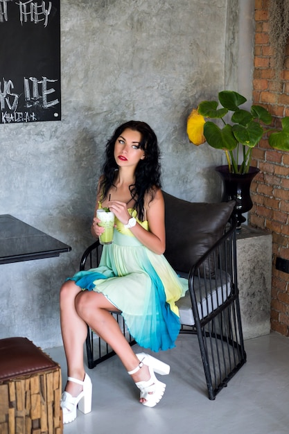 Jeune Femme Jolie Brune Vêtue D'une élégante Robe D'été, Poring In Cafe, Buvant Un Délicieux Cocktail Et Attendant Ses Amis. Photo gratuit