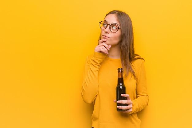 Jeune femme jolie caucasienne doutant et confus. elle tient une bière. Photo Premium