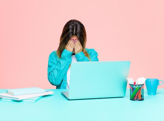 Jeune femme jolie travaillant avec un ordinateur portable se sentant triste, frustrée, nerveuse et déprimée, couvrant le visage avec les deux mains, pleurant Photo Premium