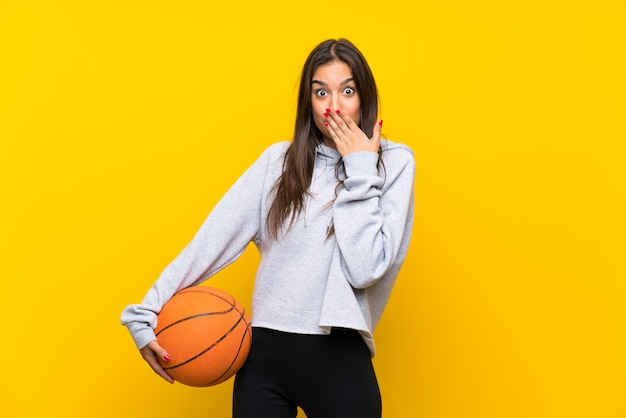 Jeune femme jouant au basketball avec une expression faciale surprise Photo Premium