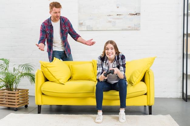 Jeune femme jouant au jeu vidéo avec son petit ami debout derrière le canapé jaune, haussant les épaules Photo gratuit