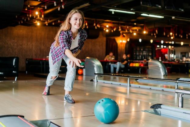 Jeune Femme Jouant Avec Une Boule De Bowling Photo gratuit