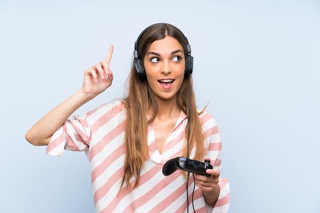 Jeune femme jouant avec un contrôleur de jeu vidéo sur un mur bleu isolé dans le but de réaliser la solution tout en levant un doigt Photo Premium