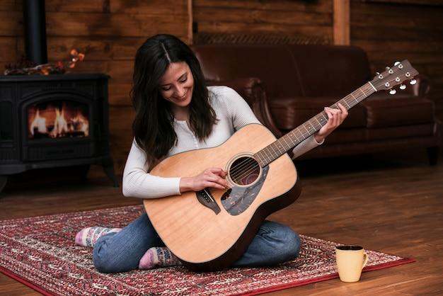 Jeune femme jouant de la guitare à la maison Photo gratuit