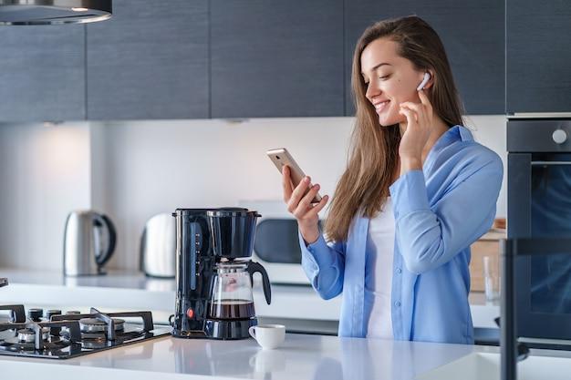 Jeune Femme Joyeuse Joyeuse écoute Livre Audio à L'aide D'écouteurs Sans Fil Blancs Et Smartphone Dans La Cuisine à La Maison. Personnes Mobiles Photo Premium