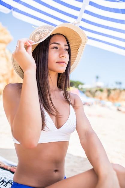 Jeune Femme Latine Beauté En Bikini Et Chapeau De Paille Assis Sous Un Parasol Sur La Plage Près De La Côte De La Mer. Photo gratuit