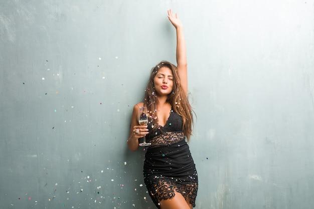Jeune Femme Latine Célébrant Le Nouvel An Ou Un événement. Excité Et Heureux, Tenant Une Bouteille De Champagne Et Une Tasse. Photo Premium