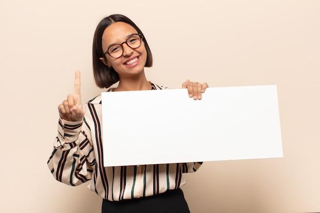 Jeune Femme Latine Souriant Fièrement Et Avec Confiance En Faisant Le Numéro Un Pose Triomphalement, Se Sentant Comme Un Leader Photo Premium