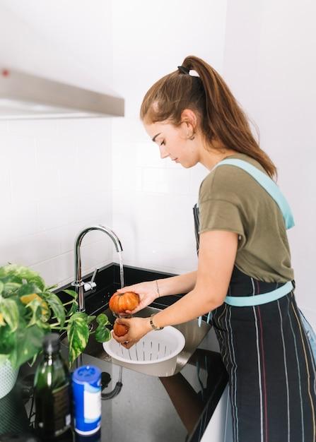 Jeune femme, laver, tomates, dans, les, évier cuisine Photo gratuit