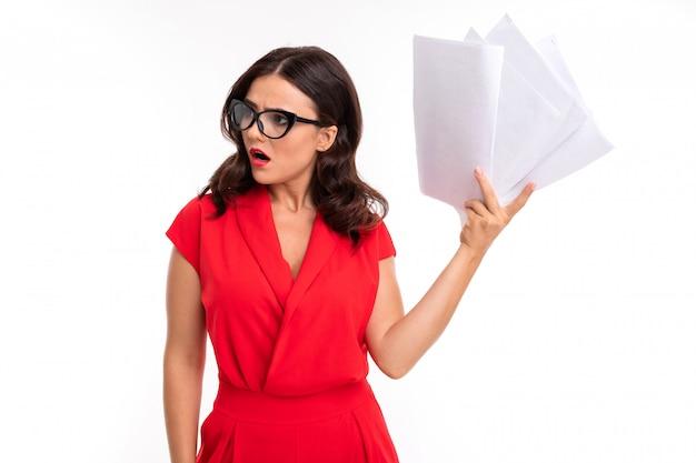 Une Jeune Femme Avec Des Lèvres Rouges, Un Maquillage Lumineux, Des Cheveux Longs Ondulés Sombres, Dans Un Costume Rouge, Des Lunettes Noires Avec Des Piles Transparentes, Tient Des Papiers Et Est Surprise Photo Premium