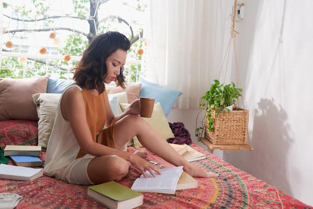 Jeune femme lisant un livre assis sur son lit avec une tasse de boisson Photo gratuit