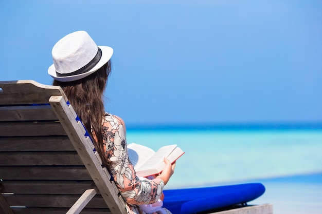 Jeune femme lisant un livre sur les vacances d'été à la plage blanche Photo Premium