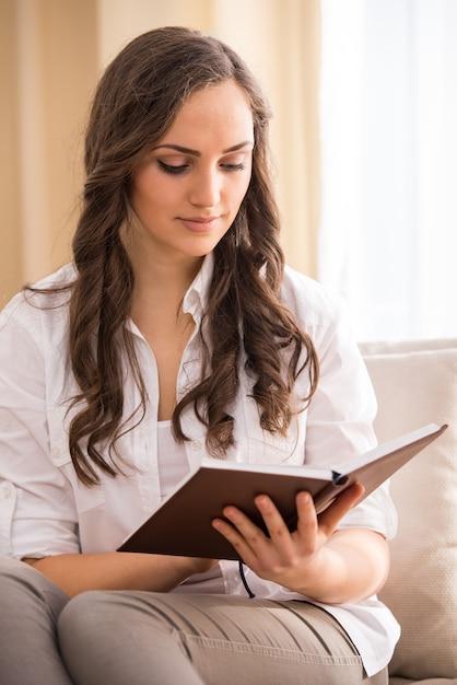 Jeune femme lit un livre sur le canapé. Photo Premium