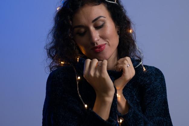 Jeune femme avec les lumières rougeoyantes de noël célébration. Photo Premium