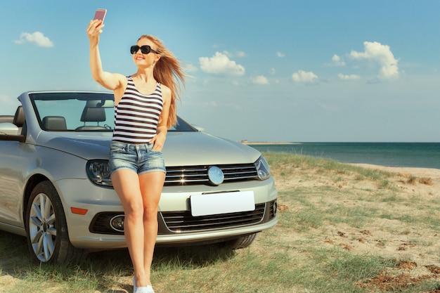 Jeune femme à lunettes de soleil faisant autoportrait Photo Premium